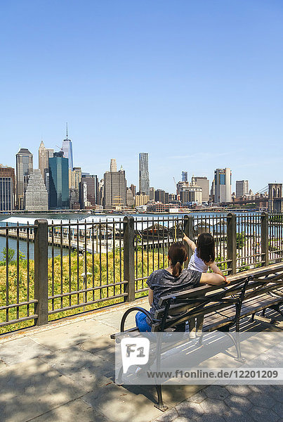 USA  New York  Brooklyn  Back view of woman and young girl sitting on bench while looking the skyline of Manhattan from Brooklyn