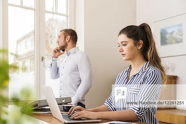 Junge Frau  die zu Hause an ihrem Laptop arbeitet