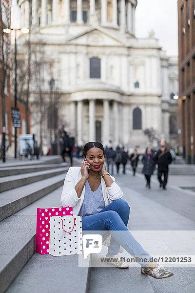 UK  London  Frau mit Einkaufstaschen auf dem Handy auf der Treppe in der Stadt sitzend