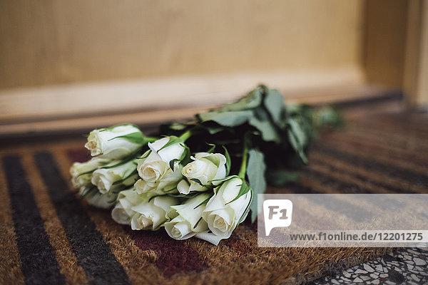 Strauß weißer Abschiedsblumen auf Bodenmatte an der Wohnungstür des verstorbenen Nachbarn liegend