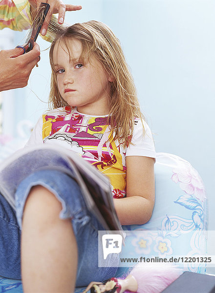 Hands of hairdresser combing and cutting hair of unhappy little girl