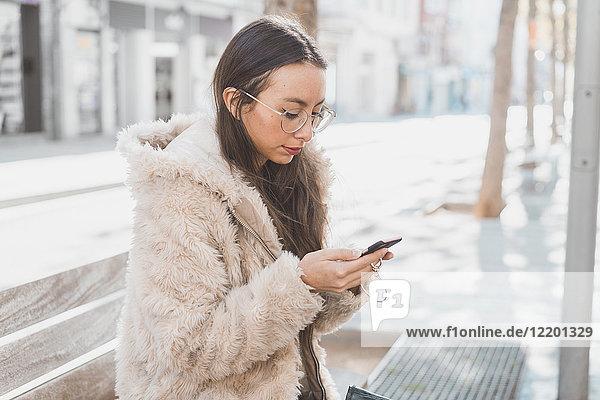 Stilvolle junge Frau in der Stadt mit dem Handy