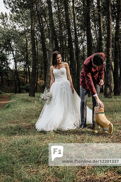 Bride and groom in forest with funny dog-shaped balloon