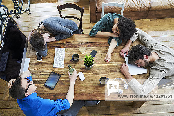 Elevated view of exhausted coworkers at wooden table in office