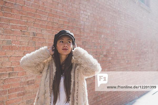 Stilvolle junge Frau vor der Backsteinmauer