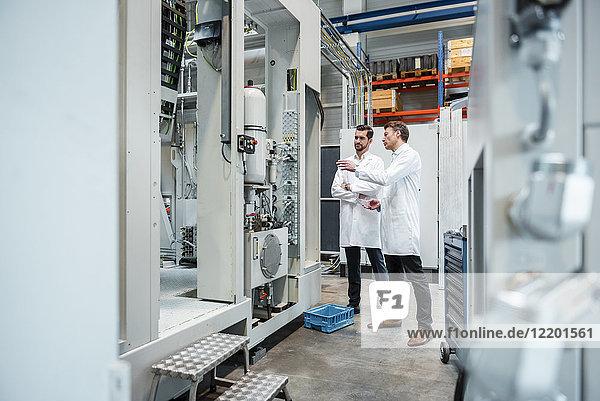 Zwei Männer in Laborkitteln reden in der Fabrik.
