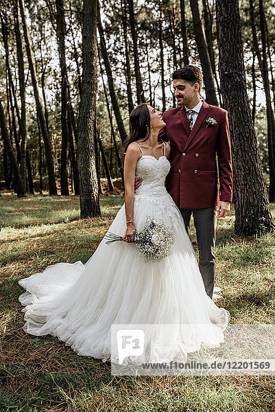 Happy bride and groom standing in forest