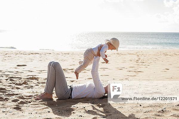 Glückliche Mutter mit kleiner Tochter am Strand