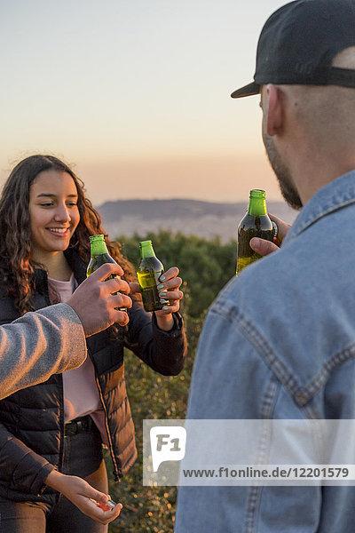 Fröhliche Freunde  die bei Sonnenuntergang im Freien Bierflaschen klirren.