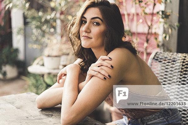 Porträt einer jungen Frau  die auf einer Bank im Freien sitzt.