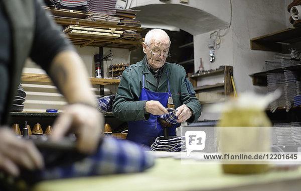 Senior-Schuhmacher bei der Arbeit an Hausschuhen in der Werkstatt Senior-Schuhmacher bei der Arbeit an Hausschuhen in der Werkstatt