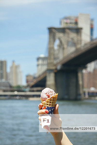 USA  New York  Brooklyn  Close up of woman hand holding a strawberry ice cream cone with Brooklyn Bridge in background