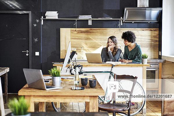 Zwei junge Frauen mit Laptop im modernen Büro