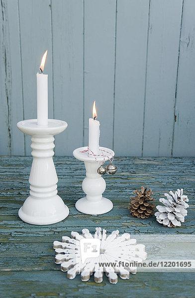 Weißes Tischset aus Wäscheklammern  weißen Kerzen  Glocken und Tannenzapfen