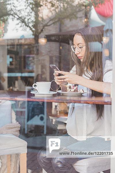 Frau mit Kuchen  die ihr Handy in einem Café überprüft.
