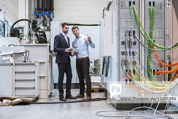 Zwei Geschäftsleute mit Tablette in der Fabrik