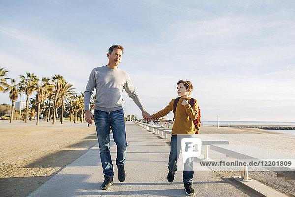 Vater und Sohn beim Spaziergang an der Strandpromenade