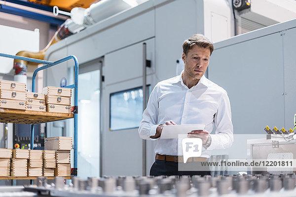 Geschäftsmann in der Fabrik hält Tablette Blick auf Maschine