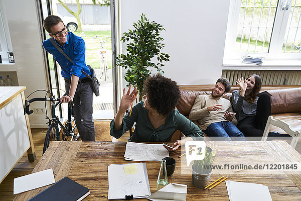 Coworkers waving at young man with bicycle arriving in modern office