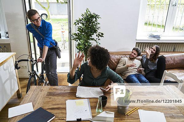 Mitarbeiter winken dem jungen Mann mit dem Fahrrad zu  der im modernen Büro ankommt