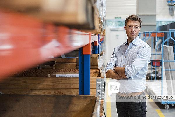 Porträt eines selbstbewussten Geschäftsmannes im Fabriklager