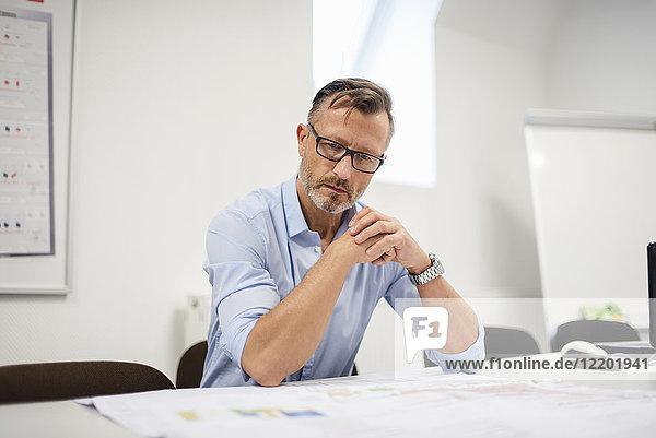 Der reife Geschäftsmann betrachtet den Plan auf dem Schreibtisch im Büro.