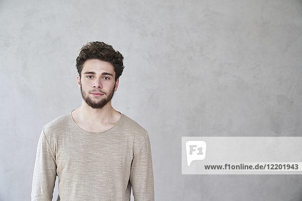 Porträt eines selbstbewussten jungen Mannes vor grauer Wand