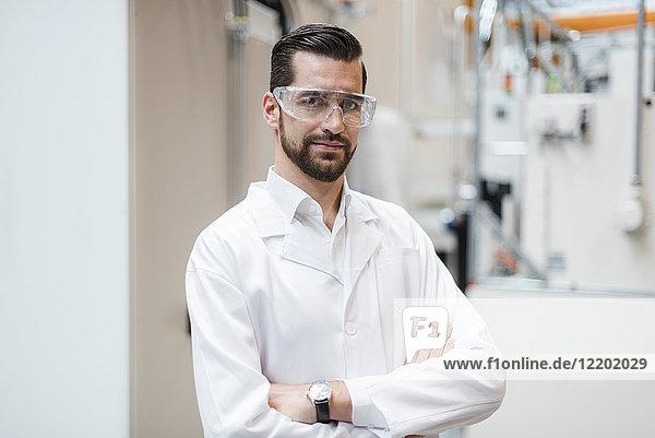 Porträt eines Mannes mit Laborkittel und Schutzbrille in der Fabrik