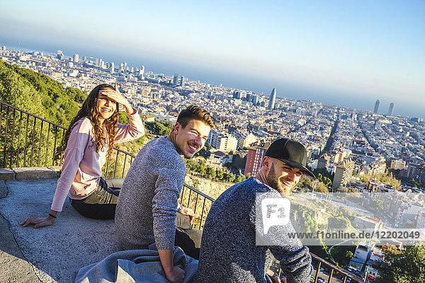 Spanien  Barcelona  drei lächelnde Freunde sitzen auf einer Mauer mit Blick auf die Stadt.