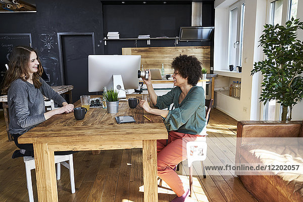 Two happy young women with camera in modern office