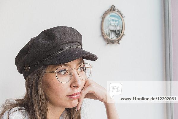 Stilvolle junge Frau mit Brille und Mütze denken