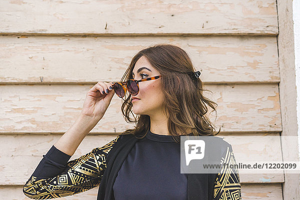 Junge Frau mit Sonnenbrille  die etwas sieht.