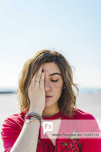 Portrait of young woman outdoors covering one eye