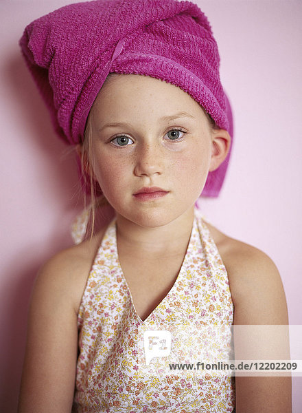 Portrait of little girl wearing pink towel turban