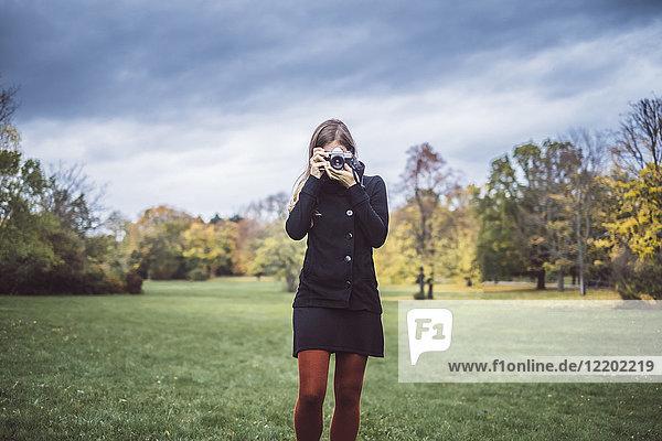 Junge Frau fotografiert mit Kamera auf einer Wiese im Herbstpark