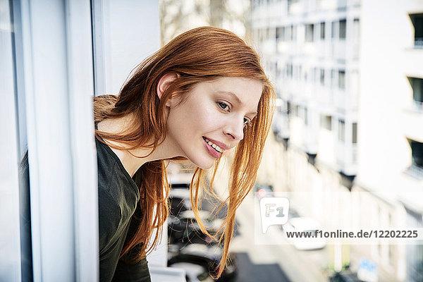 Porträt einer lächelnden rothaarigen Frau  die sich aus dem Fenster lehnt.