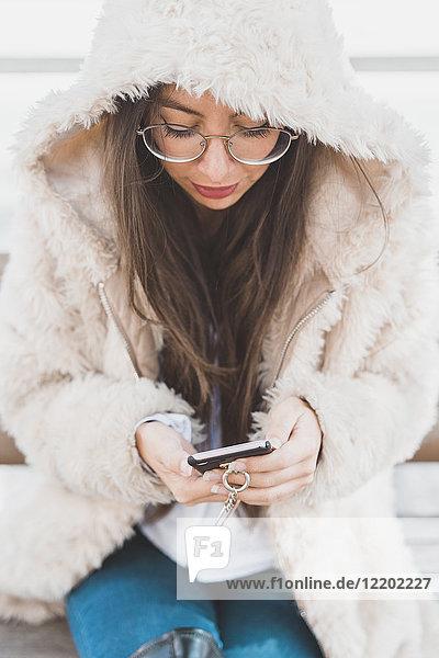 Stilvolle junge Frau auf einer Bank sitzend mit dem Handy