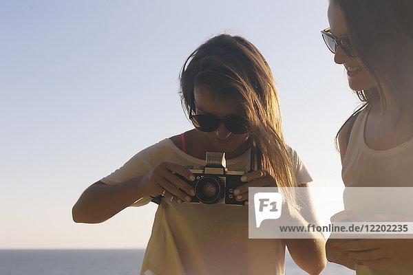 Indonesien  Bali  Lembonganische Insel  zwei junge Frauen mit Kamera am Meer