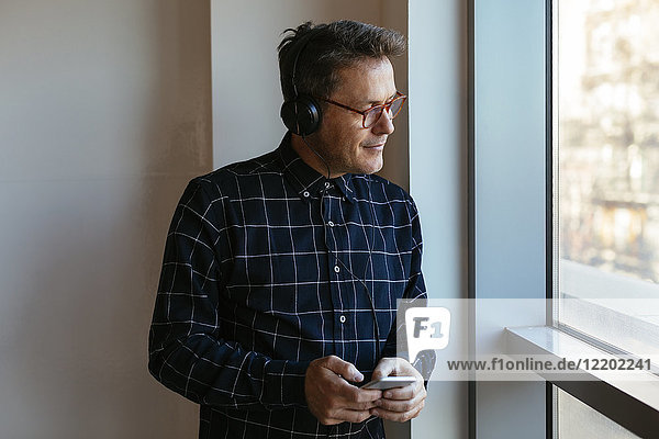 Geschäftsmann mit Kopfhörer und Handy aus dem Fenster schauend
