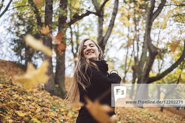 Porträt einer glücklichen jungen Frau  die Herbstblätter in die Luft wirft.