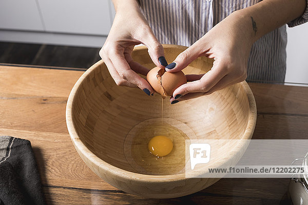 Woman breaking egg  wooden bowl