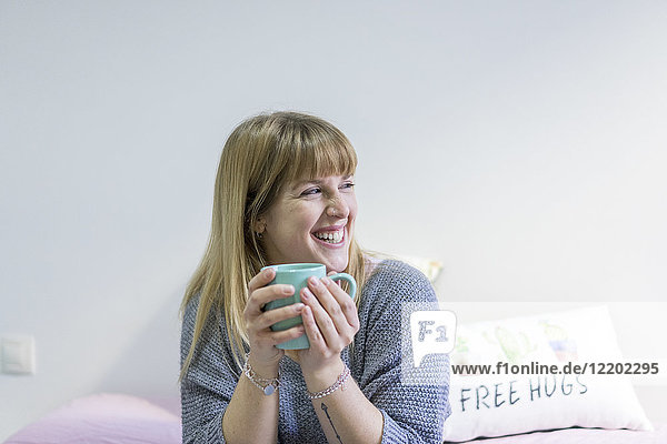Portrait of laughing young woman with coffee mug at home