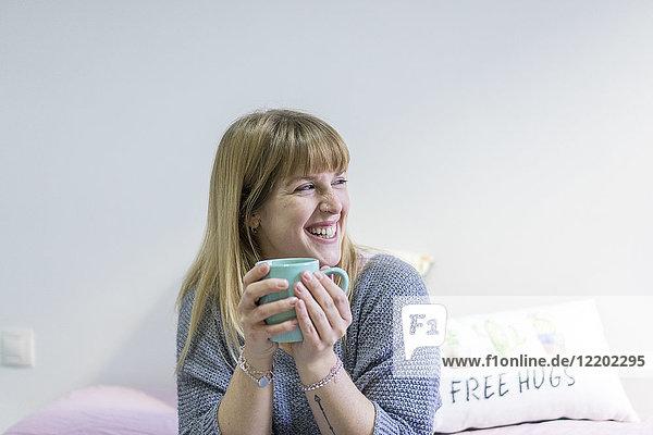 Porträt der lachenden jungen Frau mit Kaffeetasse zu Hause