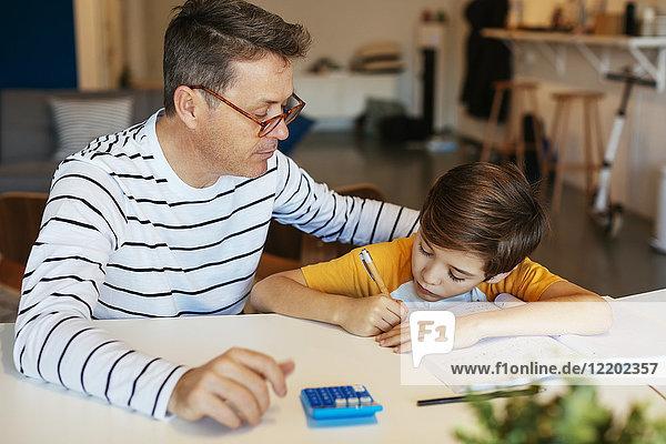 Vater beobachtet Sohn bei den Hausaufgaben am Tisch