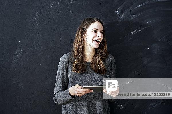 Lachende junge Frau hält Tablette vor der Tafel