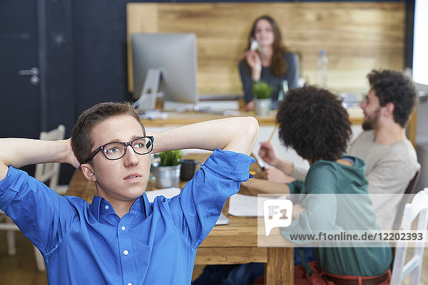 Young man thinking in office with coworkers in background
