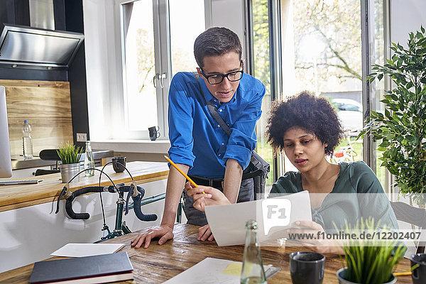 Zwei Kollegen diskutieren über Papier im modernen Büro