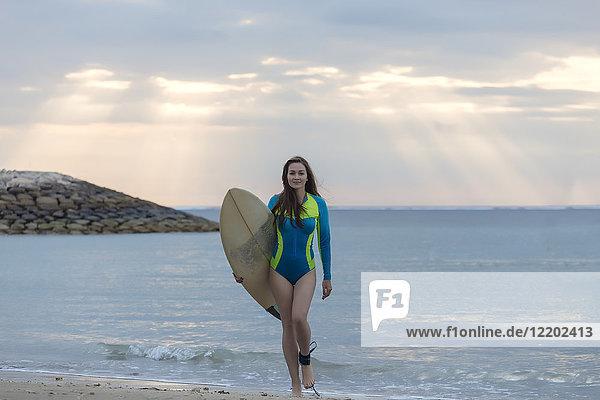 Indonesien  Bali  junge Frau mit Surfbrett am Strand spazieren gehen