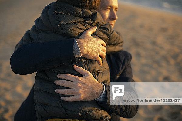 Vater umarmt Sohn am Strand