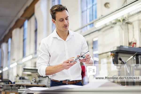 Young businessman in factory holding component